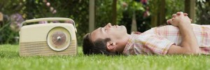 Man relaxing on lawn with old-fashioned radio